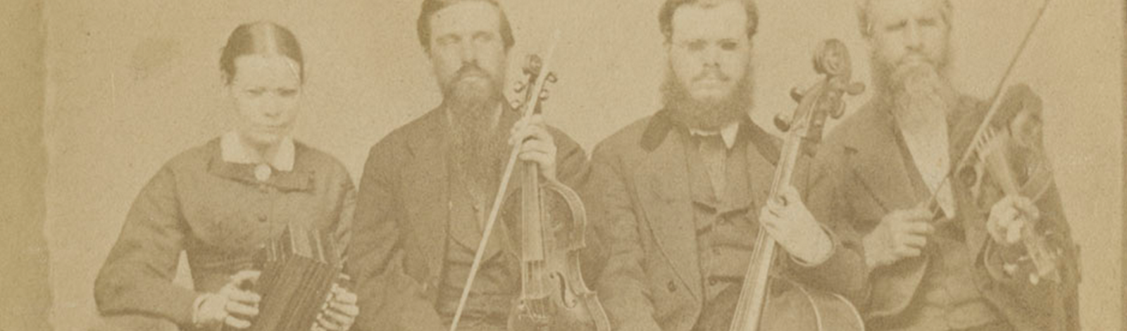 [Portrait of Hostetler family of blind musicians]. Mount Pleasant, Penna, [ca. 1866]. Picture shows one woman and three men, seated next to each other, and holding instruments. The woman holds an accordion in her lap and she looks slightly down. To her left is a man, his eyes closed, who holds a viola perpendicular to his lap with one hand and a bow in his other. To his left is a man resting a cello between his legs. He holds a bow across the base of the cello with his right hand. To his left is the last man, his eyes closed, who holds a violin by his left shoulder and a raised bow in in his right hand. The woman, as well as the man who holds a cello, wear glasses. The woman wears a dark-colored corseted dress with long sleeves and a long skirt. The men, who look toward the viewer, are bearded and wear dark-colored suits. [End of description]