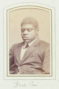 "Thomas Greene Bethune, known as Blind Tom, ca. 1870. Black & white photograph. 4 x 2.5 in. Picture depicts the carte-de-visite portrait photograph of musician Thomas Greene Bethune, later Wiggins, known as Blind Tom. Shows the young African American man from his waist up, his body slightly angled to the viewer's right. His tightly curled hair is shortly cropped. His eyes are closed. He wears a white shirt with a turned down collar. Under the collar is a dark cross tie. He also wears a dark jacket with wide notch lapels, several creases around the waist, and the top button fastened. The photograph is framed within a rectangular shape printed with a thick gold line surrounded by a thin black line. The frame is on light-colored paper. The top edge of the frame is slightly rounded. Hand written text below the portrait reads: ""Blind Tom"" [End of description]"