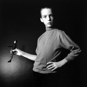 Picture shows a lanky older boy from his upper legs up. He stands, his arms posed, and looking directly at the viewer. His hair is combed severely back from his face. His body is slightly angled away from the viewer. The left part of his face is partly in shadow. His left arm is bent at the elbow and his left hand rests on his hip. His right arm lies close to his body. It is bent at the elbow at a right angle to his body. His right hand is extended and he holds a Catwoman doll in a similar pose to himself. He wears a dark-colored turtleneck, with the sleeves slightly pushed up, and black pants. [end of description]