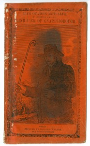 "Picture shows the illustrated orange paper cover of a booklet. The illustration fills most of the cover and shows a three-quarter length engraved portrait of a man, presumably John Metcalfe. The man stands, his eyes closed, and faces slightly away from the viewer. He holds a staff in his right hand. Both of his arms are bent at the elbow, in an L-shape, and rest at the side of his body. He is attired in 18th-century clothing. He wears a dark-colored slightly floppy hat, a white cravat, and a dark-colored vest under a dark-colored overcoat with wide collars and wide hip pockets. Engraved lines resembling scratch marks give the man's hat and clothing texture. In the far left background is a cluster of trees. Above the man are multiple rows of horizontal parallel lines with two unlined areas forming the shapes of clouds. A black-colored stain runs vertically down the center of the image, slightly obscuring the portrait. The title text ""Life of John Metcalfe. [next line] Commonly Called [next line] Blind Jack of Knaresborough,"" sits above the illustration and in the upper edge of the cover. Below the illustration is the text of the imprint: Otley: [next line] Printed by William Walker. [next line] Sold by the Bookseller. A rectangular-shaped border comprised of inter-twirled lines surrounds the illustration, title and imprint. [End of description]"