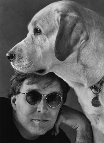 Picture shows bust-length portrait of Stephen Kuusisto with his dog. In the lower left edge of the image to the viewer, Kuusisto rests his left cheek on the knuckles of his left hand. He wears dark-shaded glasses and a black T-shirt. Above his head is the head of a yellow labrador posed in left profile. The dog wears a metal choke collar with a dog tag.