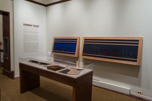 """Picture shows Jaynes's Gift #2, an interactive piece inspired by the physicality of the wooden writing frames and the abstract quality of letterforms written in the 1870s by Jennie Partridge who was blind. It is two oversized, horizontal writing frames, with felt backgrounds, mounted alongside one another on an off-white painted wall. Beneath the top of the frame are two evenly spaced horizontal wooden strips. Then there is a wider space and another horizontal strip. The left frame, with blue felt, serves as a mount for free standing, abstract letterforms constructed in darkly painted wood. The letters in the large frame on the right, with black felt, are more formally set within their indented image. The elaborate, enlarged letter forms spell out the phrase: """"I know."""" In the foreground is a case with historical materials. In the left background is the introductory text to the exhibition."""